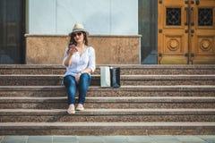帽子和太阳镜的美丽的深色的女孩坐与一个电话的步在手上 免版税库存照片