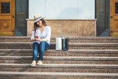 帽子和太阳镜的美丽的深色的女孩坐与电话的步在手和微笑上 免版税库存照片