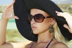 帽子和太阳镜的美丽的白肤金发的妇女在beach.paradise海岛上 免版税库存照片