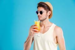 帽子和太阳镜的英俊的人喝新鲜的橙汁的 图库摄影
