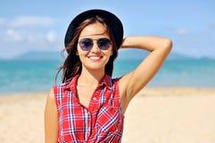 帽子和太阳镜的年轻可爱的妇女 库存图片