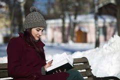 帽子和夹克微笑的阅读书的女孩坐是 免版税库存图片