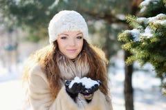 帽子和手套的少妇笑使用与雪的 免版税库存图片