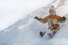 帽子和橙色连衫裤的男孩滑下在后面的雪幻灯片 画象 特写镜头 蓝色分行休息日霜谎言天空雪结构树冬天 免版税图库摄影