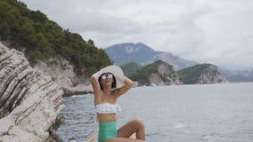 帽子和泳装的女孩坐岩石和神色在蓝色海 可爱的妇女松弛近的海 夏天 股票录像