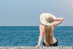 帽子和泳装的美丽的女孩坐海滩 海和天空在背景 回到视图 库存图片