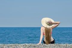 帽子和泳装的美丽的女孩坐海滩 海和天空在背景 回到视图 免版税库存照片