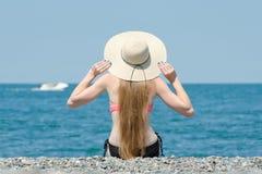 帽子和泳装的美丽的女孩坐海滩 海和小船在背景 回到视图 图库摄影