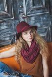 帽子和牛仔裤的美丽的卷发的女孩 免版税图库摄影