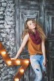 帽子和牛仔裤的美丽的卷发的女孩 免版税库存图片