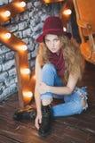 帽子和牛仔裤的美丽的卷发的女孩 库存照片
