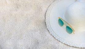帽子和玻璃位于海滩,蓝色海,日间松弛或长的假日 免版税库存图片