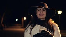 帽子和白色外套的深色的女孩喝咖啡并且在夜公园微笑 股票视频