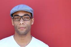 戴帽子和眼镜的简单的衣裳的一个英俊的年轻人 免版税图库摄影