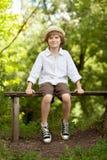 帽子和短裤的男孩坐长凳 库存照片
