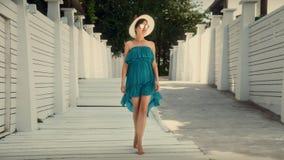 帽子和礼服的一个女孩在白色步走 休息在旅馆 免版税库存照片