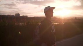 帽子和背包的一个年轻人去以日落光的城市为背景 疯狂的风景 影视素材