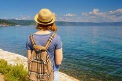 帽子和背包的非离子活性剂旅游女孩敬佩贝加尔湖的美好的风景从利斯特维扬卡村庄江边的晴朗的 库存图片