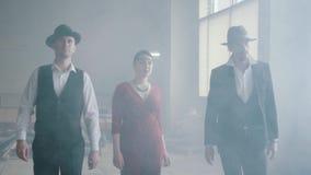 帽子和衣服的两个确信的红色礼服的男人和妇女今后走一个被放弃的大厦的 在空的黑手党 股票视频