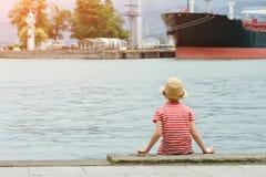 帽子和镶边T恤杉的男孩坐海滩和神色在船 回到视图 免版税图库摄影