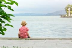 帽子和镶边T恤杉的男孩坐海滩 回到视图 免版税库存照片