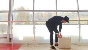 帽子和黑衣服的一个时髦的人在银行并且投入金钱美元在手提箱,慢mo,更加富有 影视素材