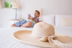 帽子回来在白色床上在旅馆和人用途手机里 库存照片