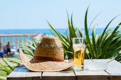 帽子在一杯古巴libre旁边投入了桌 免版税库存图片