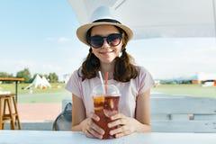 帽子太阳镜的年轻少年女孩微笑和喝凉快的莓果鸡尾酒的在室外咖啡馆的一个热的夏日 库存照片