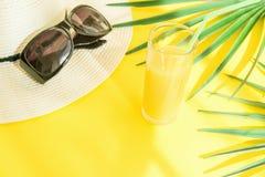 帽子太阳镜高玻璃的平的位置安排与新鲜的柑橘热带水果汁棕榈叶的在黄色背景 阳光 免版税库存照片
