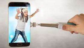帽子狼的一个男孩通过电话屏幕惊吓 免版税库存照片
