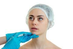 帽子的一个女孩做的医疗面部射入是在白色背景 库存图片