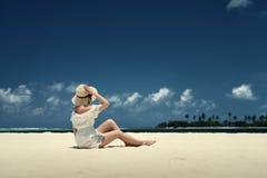帽子的一个女孩坐海滩 马尔代夫 沙子白色 免版税图库摄影