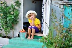 帽子的一个小,俏丽的女孩会集了成熟红色汤姆收获  库存照片