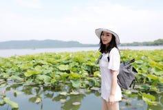 帽子的一个愉快的秀丽女孩和太阳镜在夏天庭院莲花领域旅行由湖xihu杭州 免版税库存图片