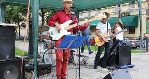 帽子的一位吟呦诗人唱歌曲并且弹在街道上的吉他 股票录像