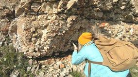 帽子的一位白肤金发的女孩摄影师拍在一个奇怪的姿势的一张照片在她的数字照相机有岩石背景  股票录像