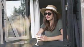 帽子的一名妇女看在与一杯的窗口外面红酒 股票录像