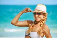 帽子的一名微笑的俏丽的妇女坐海背景 免版税库存照片