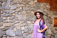 帽子的俏丽的女孩在岩石墙壁附近 免版税库存照片