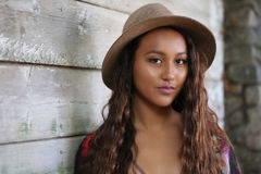 帽子的俏丽的女孩由木墙壁 免版税库存照片