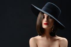 戴帽子的可爱的妇女摆在黑背景 免版税库存照片