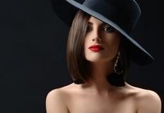 戴帽子的可爱的妇女摆在黑背景 库存图片
