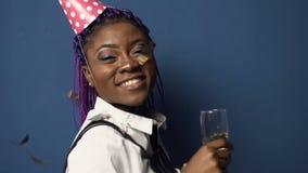 帽子的可爱的非洲女孩有在手中champanage玻璃的,获得乐趣和跳舞,当飞行下来在时的五彩纸屑 影视素材