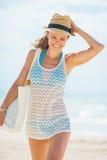 帽子的和有袋子的走在海滩的愉快的少妇 库存照片