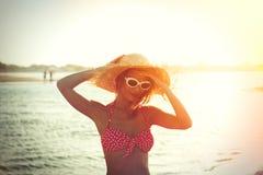帽子的在Elafonissi的女孩和比基尼泳装在日落靠岸 免版税库存图片