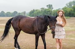 帽子的女孩和夏天穿戴与马 免版税库存照片