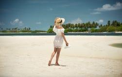 帽子的女孩和白色在海滩穿戴 在海洋的岸 马尔代夫,海岛 假期,旅行 免版税库存图片