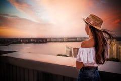 帽子的女孩在与飞行头发的日落 免版税库存照片
