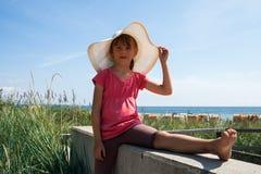 帽子的逗人喜爱的女孩在海滩 图库摄影